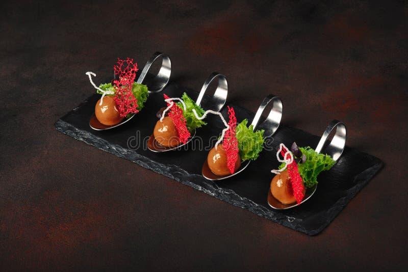 Anatra moderna molecolare del galantine di cucina in cucchiai sulla pietra e sulla r fotografia stock