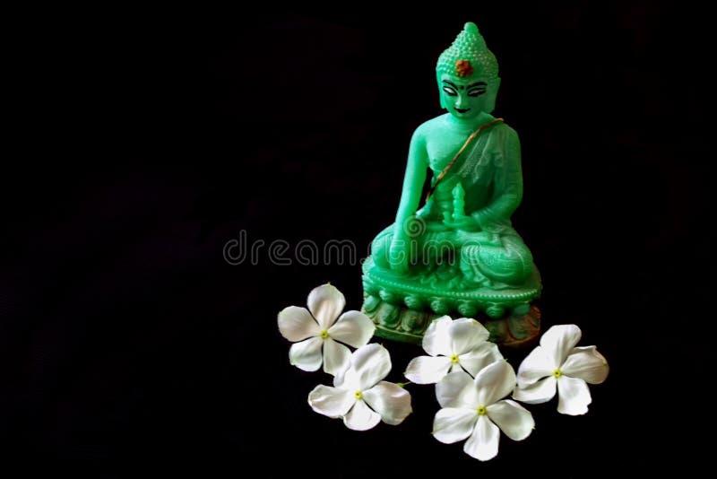 Anbietende weiße Blumen zur Statue von Lord Buddha machten vom grünen Stein stockbild