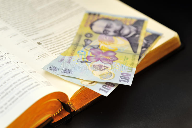 Anbietendes rumänisches Bargeld und heilige Bibel stockbild