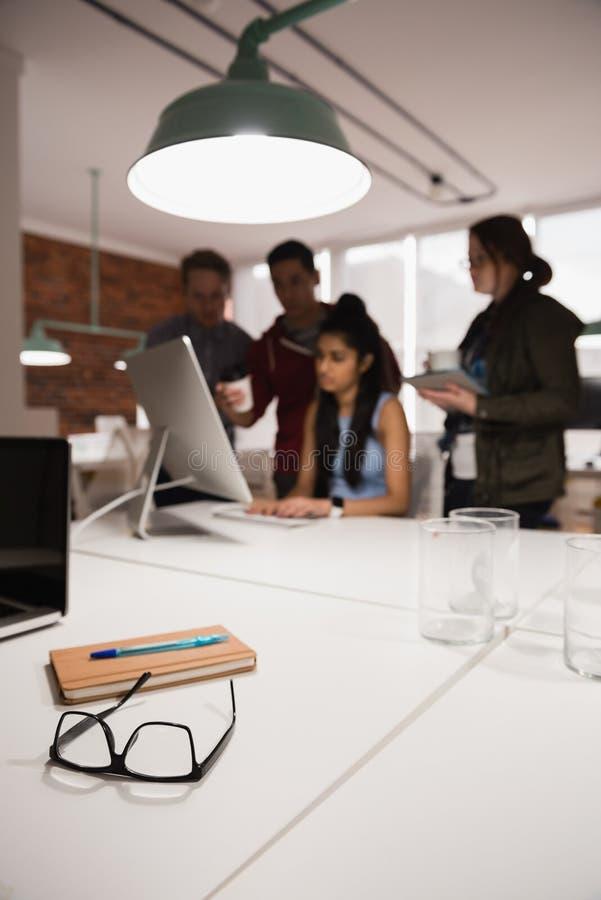 Anblickar med anteckningsboken på tabellen medan kollega som diskuterar i bakgrund fotografering för bildbyråer