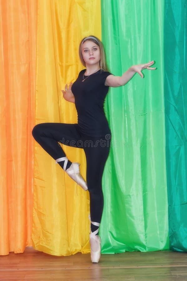 Ancer en un traje de sudor negro, se está colocando en sus dedos del pie en un ballet fotografía de archivo libre de regalías