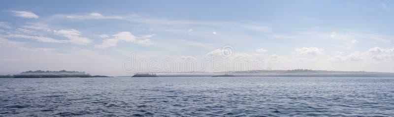 Anche paesaggio del lago con le onde, sull'orizzonte una riva rocciosa con gli alberi nella nebbia e nel cielo con le nuvole Pano fotografie stock
