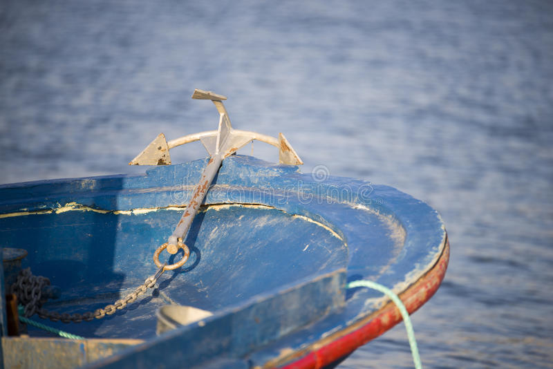Anchor and boat. Anchor and a blue fishing boat royalty free stock photography