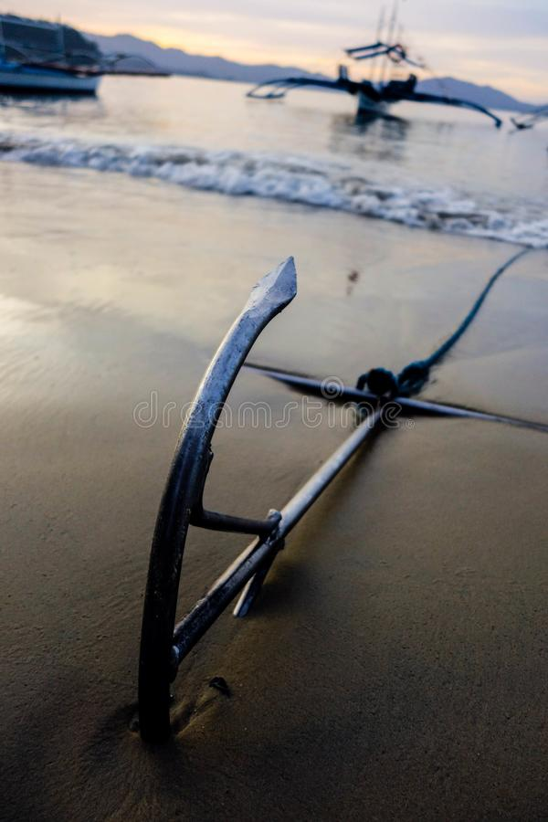 Anchor and a boat. An anchor with a boat in distance royalty free stock photos