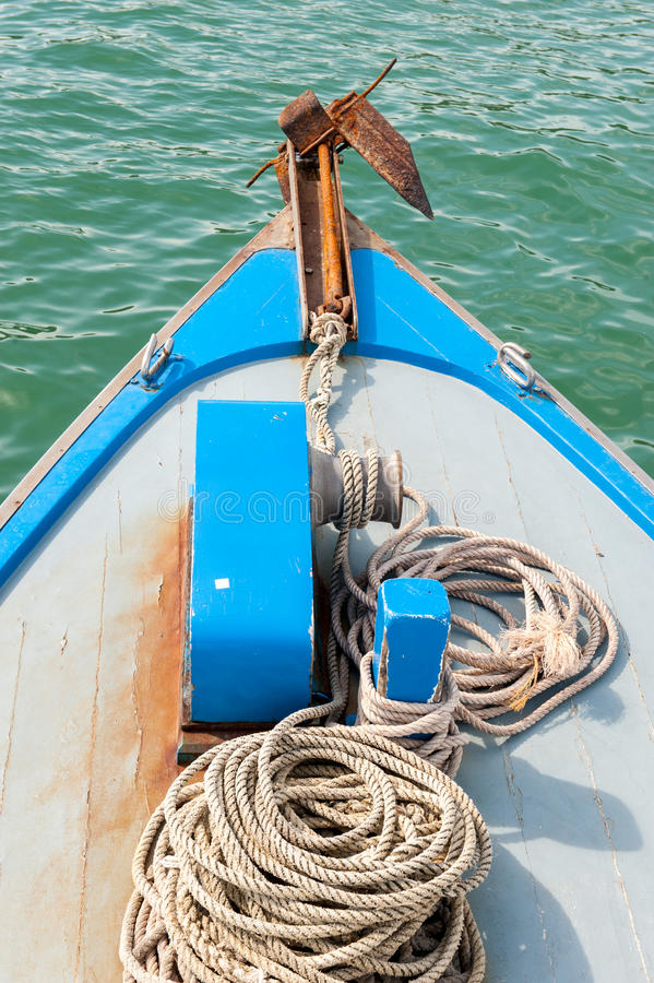 Anchor on boat. Rusty anchor on the front of a blue wooden boat royalty free stock image