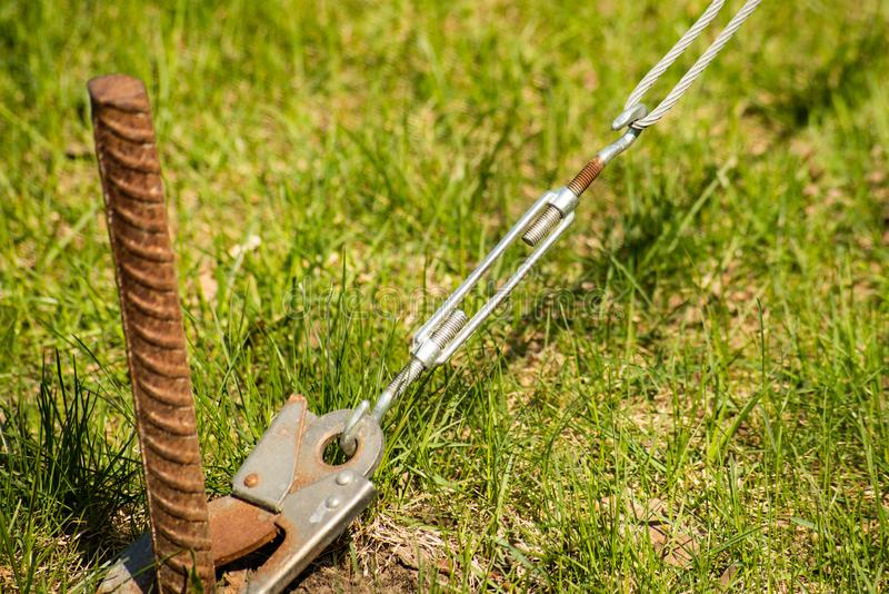 Anchor hook keeps cable attached to a metal peg in the ground. Is close, bolt, steel, screw, industry, construction, equipment, industrial, iron, tool, object stock photo
