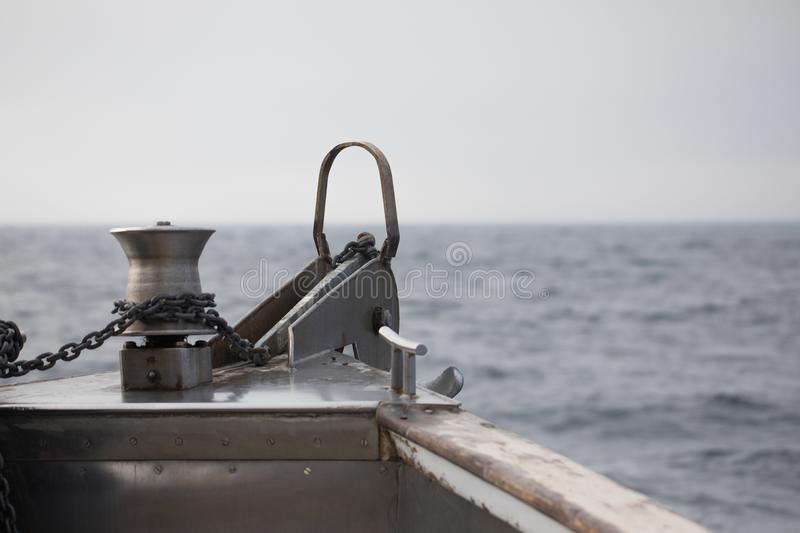 Anchor off the bow of a boat. With ocean background bokeh stock photo