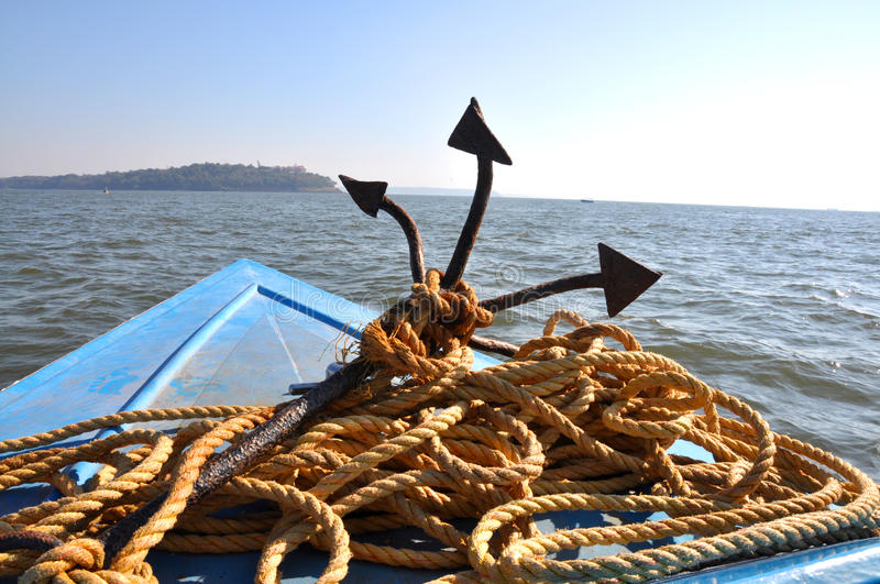 Anchor and rope. Image showing an anchor with rope placed on the head of motorboat in the sea royalty free stock photos