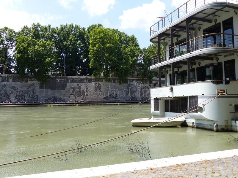 Anchored boat with the monumental mural of William Kentridge long the Tiber of Rome, Italy. royalty free stock photo