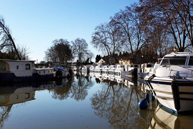 Anchored boats in the Canal du Midi. View on anchored boats in the Canal du Midi royalty free stock photography