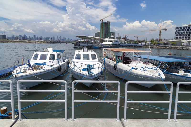 Anchored boats in Manila bay pier port, Pasay, Philippines. Blue sky royalty free stock photography