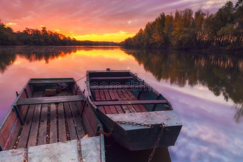 Anchored boats on the river with dramatic, gorgeous sunrise stock images