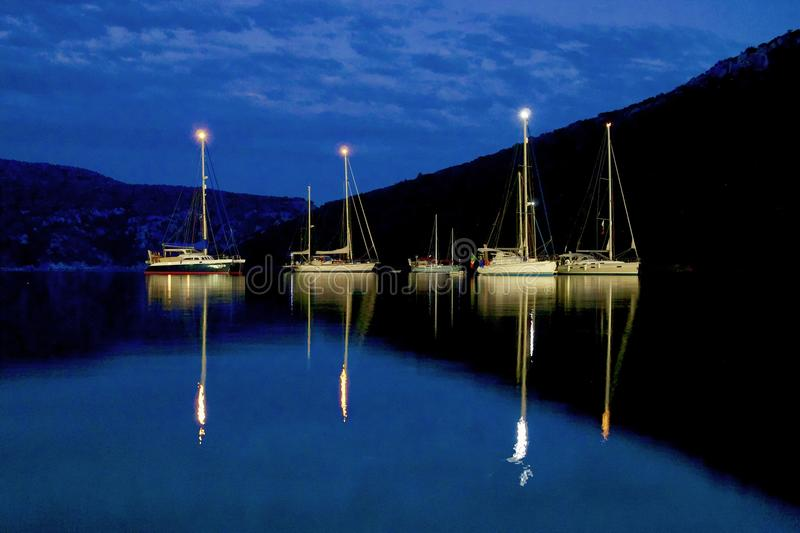 Moonlit sailboats on the sea at night royalty free stock photography