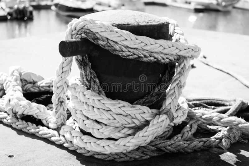 Black and White Photograph of a nautical anchoring rope for a submarine docked. Anchoring rope wrapped and secure on a dock royalty free stock photography