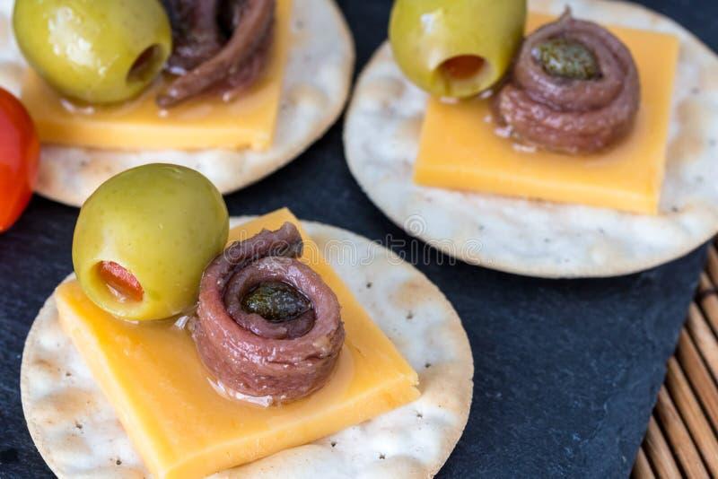 Anchova em biscoitos com azeitonas enchidas - fundo w do aperitivo imagens de stock royalty free