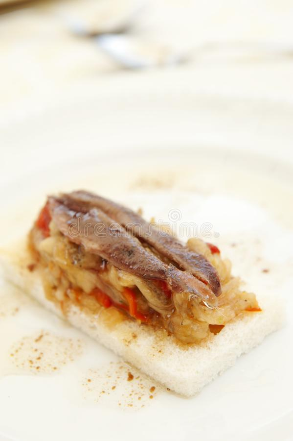 Anchovy spanish toast. Anchovy, red pepper and onion spanish toast royalty free stock image