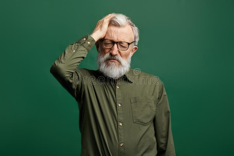 Ancião atrativo no sofrimento verde do t-shirt da dor de cabeça, pressão intracranial fotografia de stock royalty free