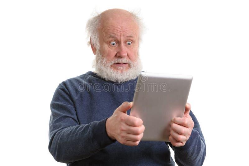 Ancião chocado engraçado que usa o tablet pc isolado no branco fotografia de stock royalty free