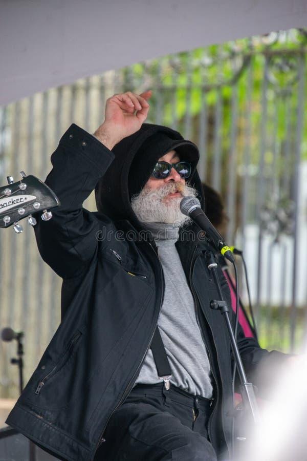 Ancião com a barba branca longa e bigode que veste um revestimento preto com uma capa fotografia de stock
