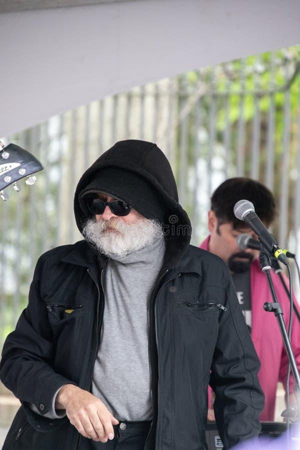 Ancião com a barba branca longa e bigode que veste um revestimento preto com uma capa fotos de stock royalty free