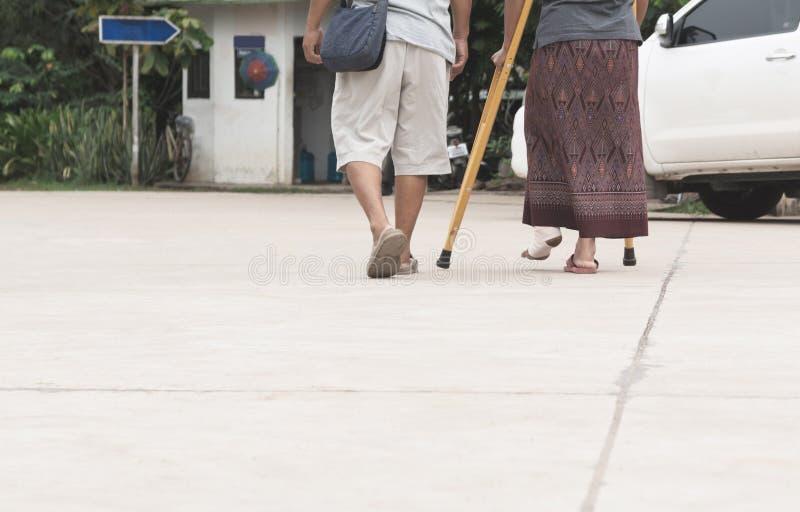 Ancião com caminhada da mulher adulta do pé quebrado junto imagem de stock royalty free