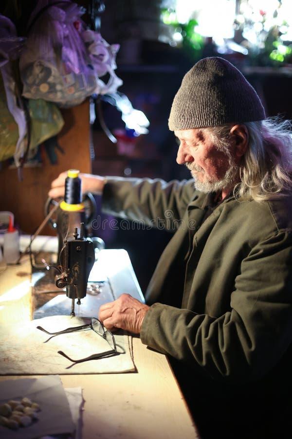 Ancião com máquina de costura imagem de stock