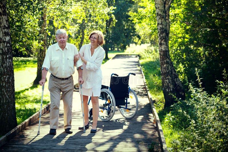 Ancião com muletas e jovem mulher no parque imagem de stock