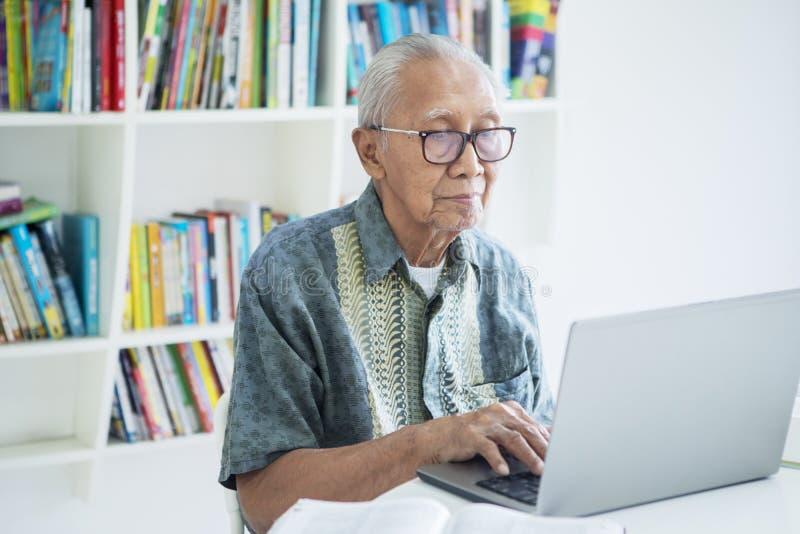 Ancião com o cabelo cinzento que trabalha na biblioteca imagem de stock royalty free