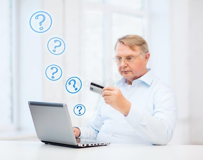 Ancião com portátil e cartão de crédito em casa fotos de stock