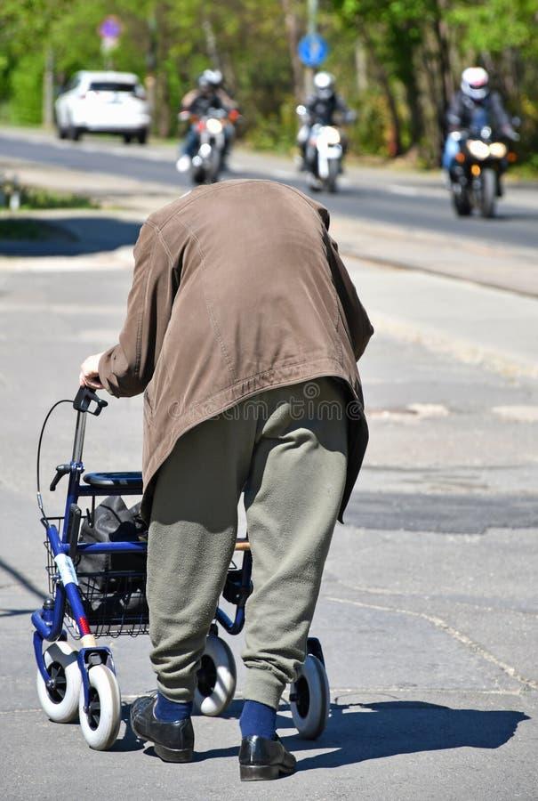 Ancião com um caminhante rodado na rua imagens de stock