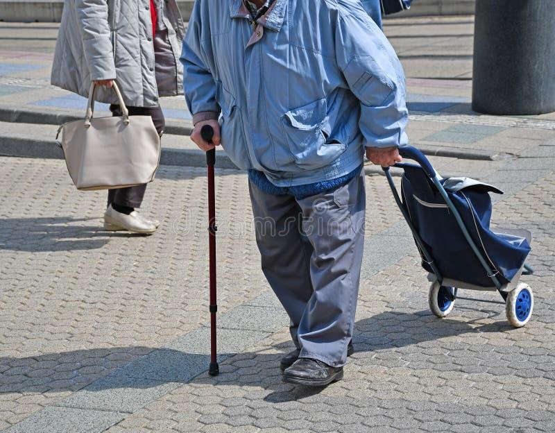Ancião com um saco de compras rodado na rua foto de stock royalty free