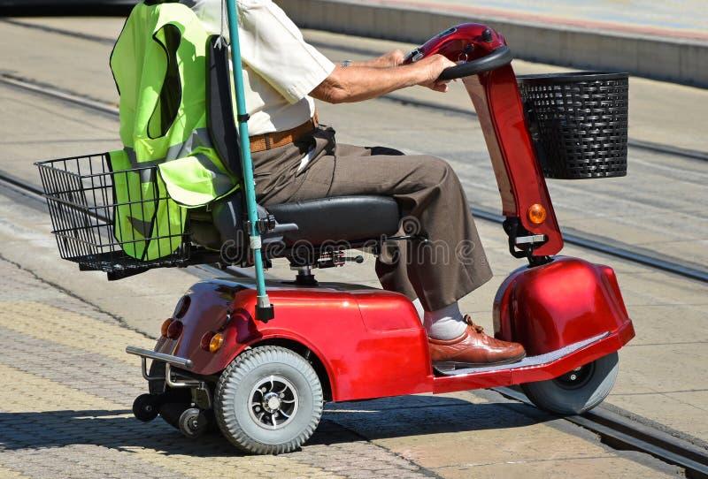 Ancião com uma cadeira de rodas elétrica fotos de stock