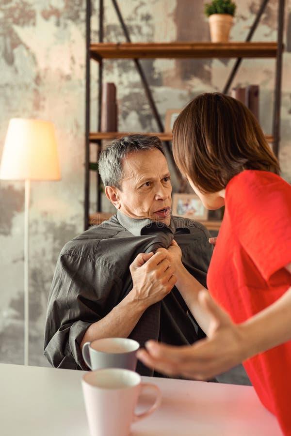 Ancião de cabelos curtos que fala pacificamente a sua esposa imagens de stock royalty free