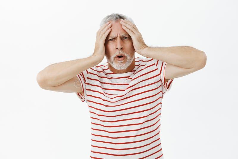 Ancião desagradado incomodado e chocado intenso que toca na cabeça e na boca aberta olhando de sobrancelhas franzidas que olham c imagem de stock royalty free