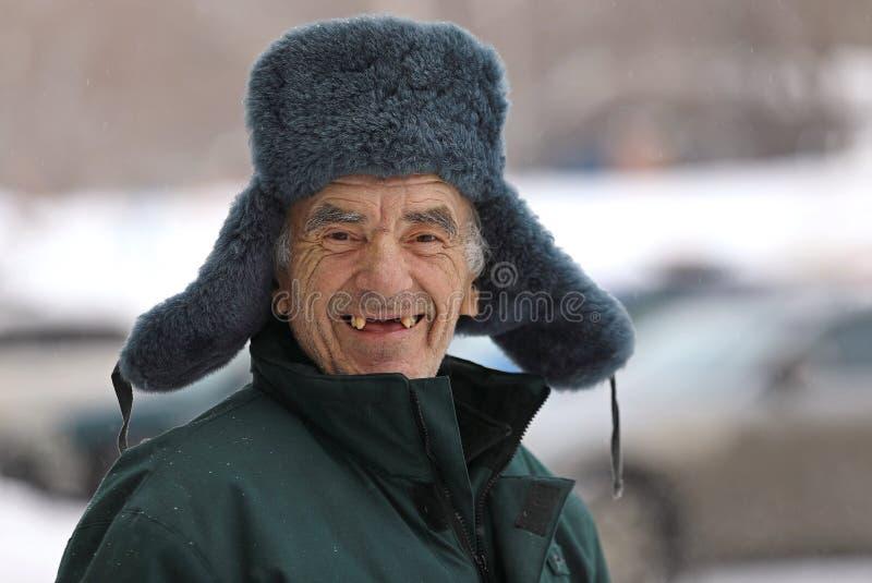 Ancião do russo em sorrisos do chapéu do inverno imagens de stock royalty free
