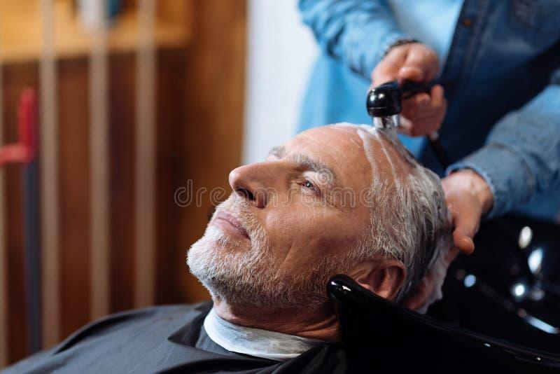 Ancião durante o lavagem de seu cabelo na barbearia imagens de stock royalty free