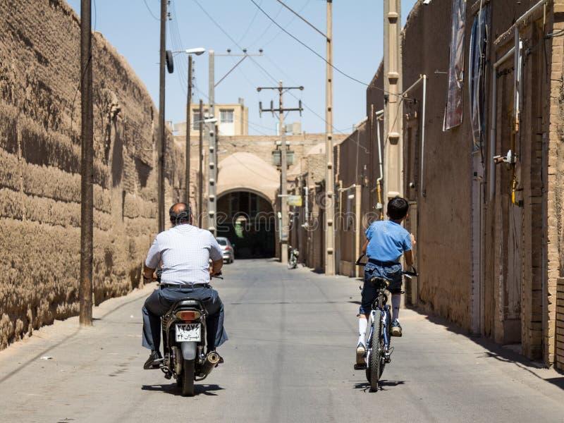 Ancião e menino novo, montando um 'trotinette' do motocycle e uma bicicleta nas ruas do Yazd velho, a cidade principal de Irã cen fotos de stock
