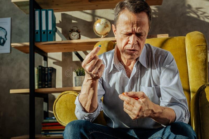 Ancião enrugado que senta-se em uma poltrona amarela e que toma comprimidos imagem de stock royalty free