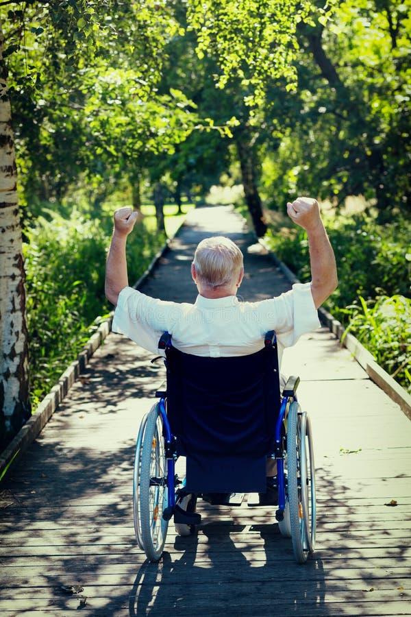 Ancião na cadeira de rodas com mãos acima imagem de stock
