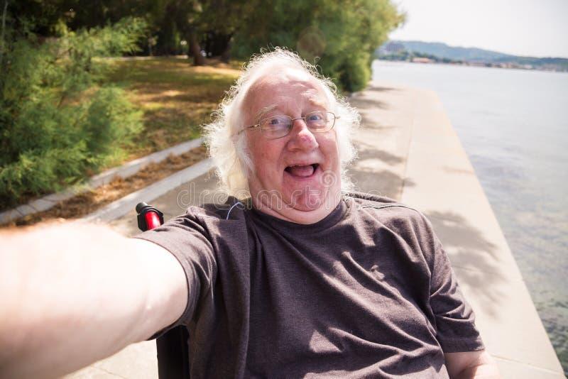 Ancião na cadeira de rodas que toma um Selfie imagens de stock royalty free