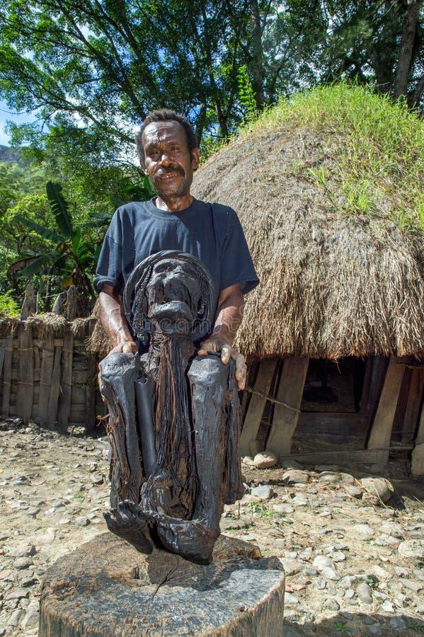 Ancião na frente de uma casa tradicional que mostra fora uma mamã de uma mamã da pessoa idosa da vila fotografia de stock royalty free