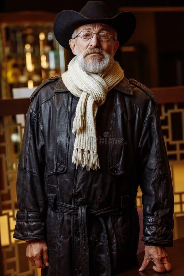 Ancião no casaco marrom e no chapéu grande que olham o suporte do quando da câmera imagem de stock royalty free
