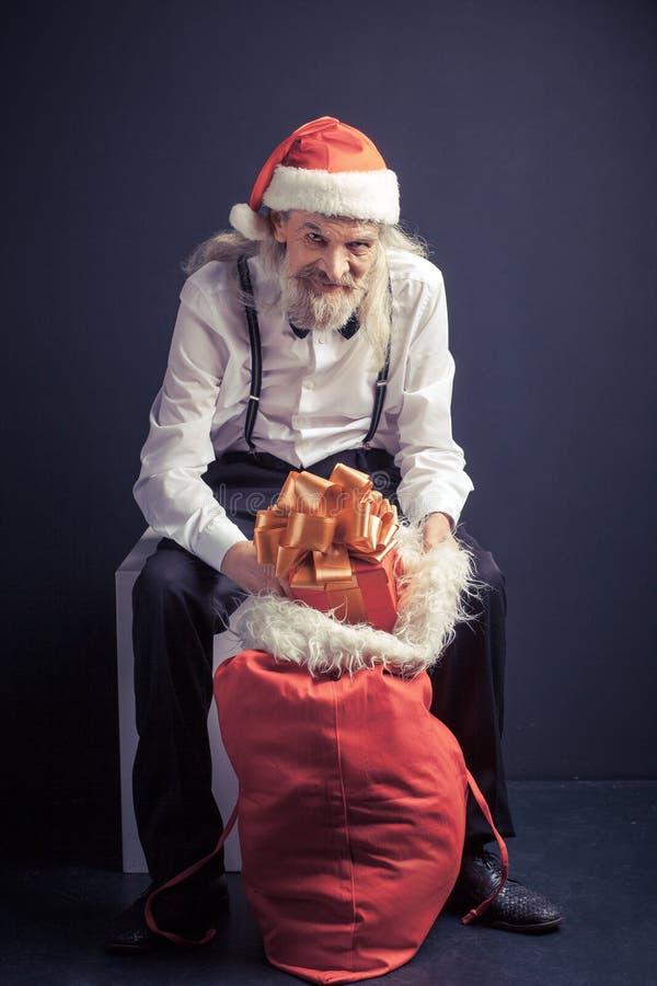 Ancião no chapéu de Santa que senta-se na cadeira com saco do presente fotografia de stock