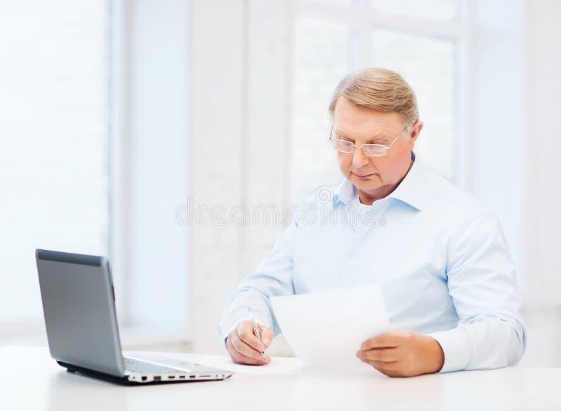 Ancião nos monóculos que enchem um formulário em casa fotos de stock royalty free