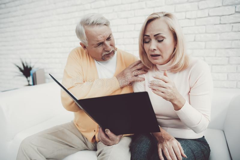 Ancião perto da mulher adulta com originais no dobrador imagens de stock royalty free