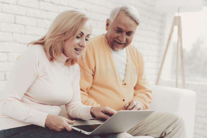 Ancião perto da mulher adulta com Smartphone e o portátil imagens de stock