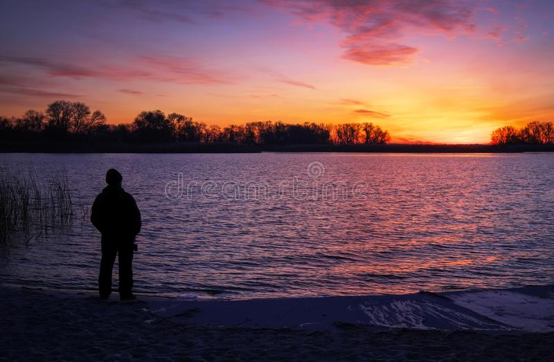 Ancião que admira o nascer do sol na praia fotos de stock royalty free