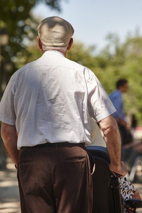 Ancião que conduz sua esposa em uma cadeira de rodas Cuidados médicos foto de stock royalty free