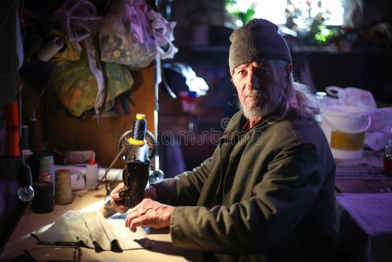 Ancião que costura em casa fotografia de stock royalty free