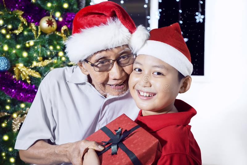 Ancião que dá a caixa de presente para seu neto fotografia de stock royalty free